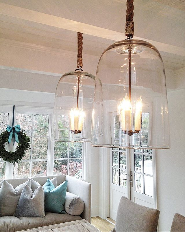 Old glass bell jars @southofmarket are suspended by rope from a painted wood plank and beamed ceiling. The old wavy glass of the bells allows the clearest of light to hover over this extended farm table.  Tis' the season for all things beautiful, white, and bright! #christmasbells #christmasseason #oldwavyglass #belljars #interiordecor #cozydining #breakfastrooms  #welllit #chandeliers #whiteandneutralpalette #antiques #frenchstyle #bluesatinsashes