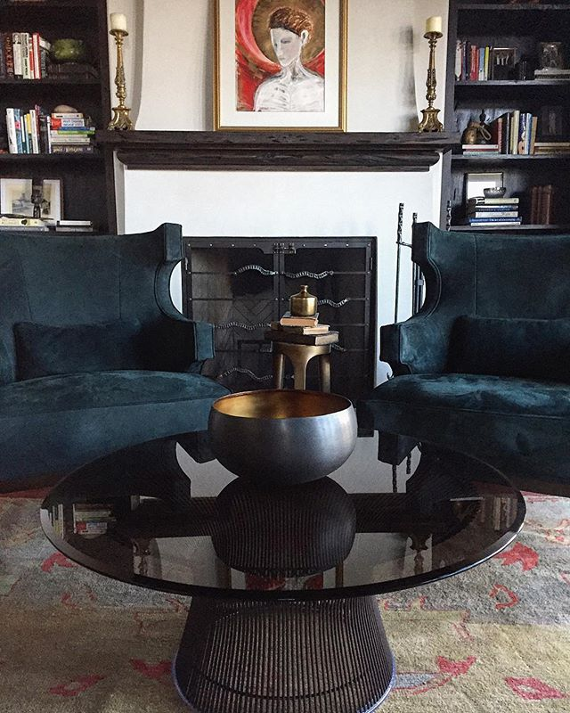 A handsome library displaying a beautiful vignette of fireside seating in thick skinned dark teal suede! The graceful yet strong sculpted arms of the chairs extend out to embrace the modern sophistication of a Knoll Platner bronze coffee table.  A collected Oushak rug and a custom hand forged fire screen finish the space with a masculine glamour!  #handsomespaces #firesideseating #studys #homelibrary #avidreader #peacefulretreat #customironwork @jacksonforge #interiorstyling @gigaram #interiordecorating #architecturalelements #curvaceous #bakerfurniture #JaquesGarcia #LuxuriousSuede #leather #thickhides #richdyelots #oushakrugs