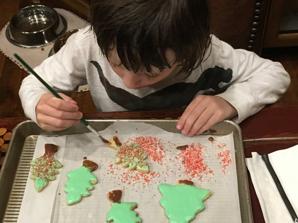 This is what decorating cookies can do for a five-year-old (our grandson, Mack). He was so serious about painting the trees!