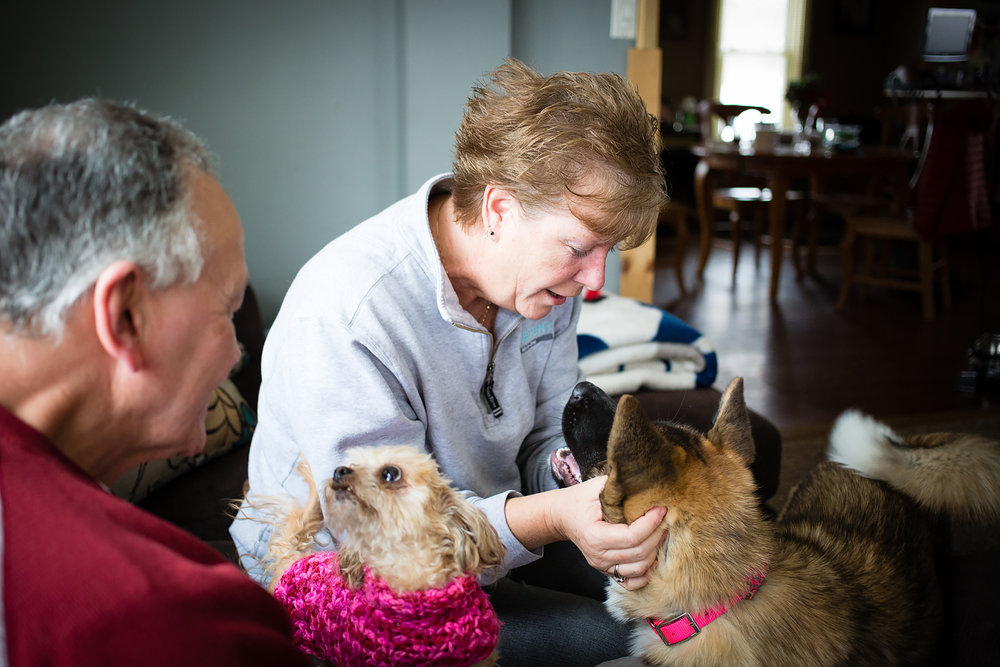Patty with their 4 month old Akita Chella while their smallest pup Mocha sits with her husband during our time together at their home in Moravia, New York // February 3, 2018.