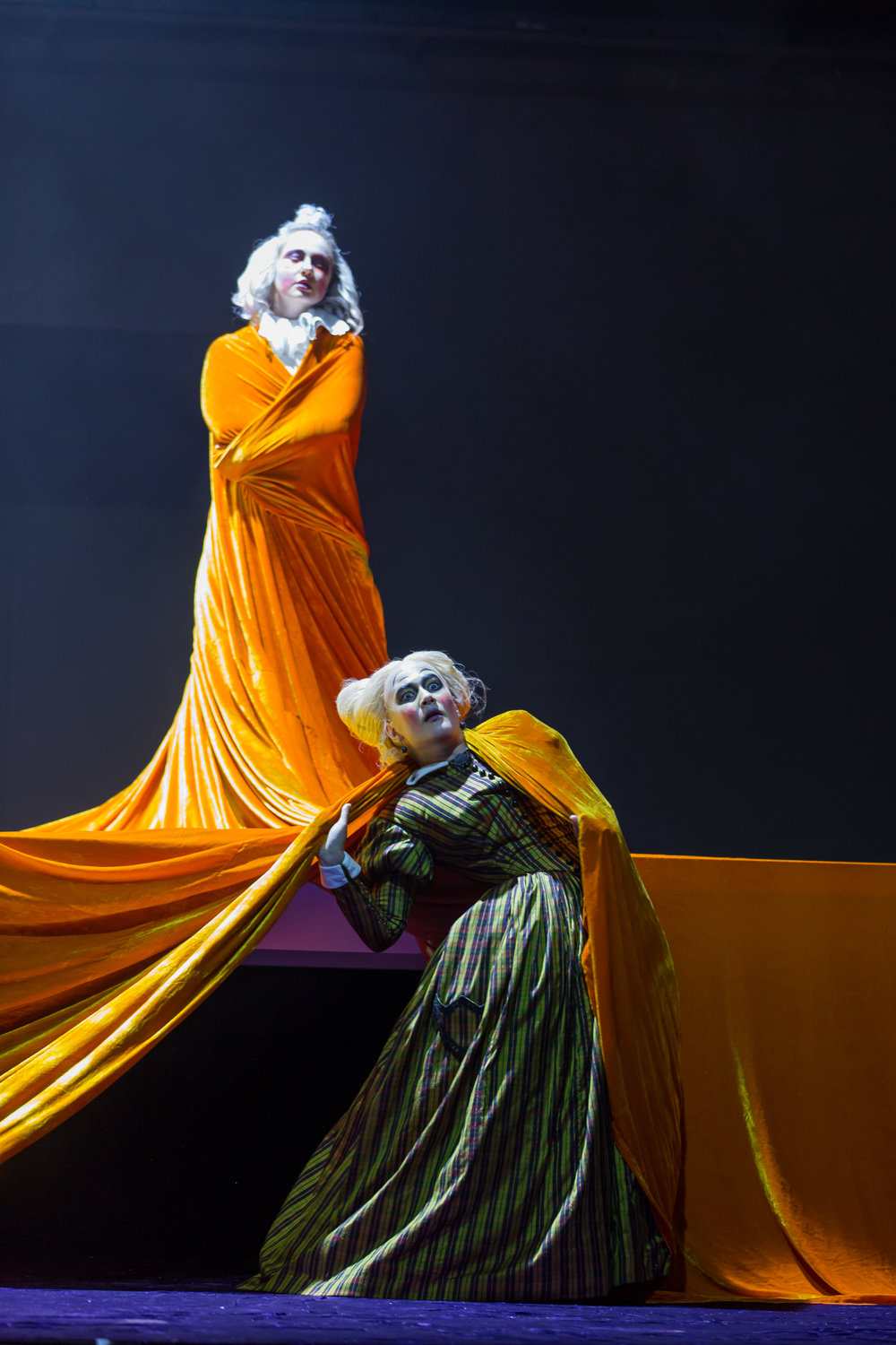 From  The Juniper Tree : Megan Mikailovna Samarin, the son, drapped by the golden tablecloth, stands triumphantly over Annie Rosen, the stepmother;  photo by Scott Suchman and courtesy of Wolf Trap Opera.