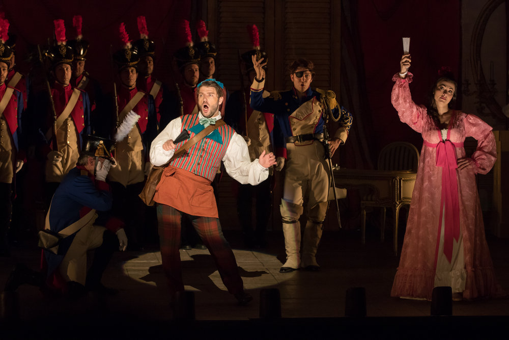 A sample of the lighting, costumes, and choreography with soldiers, Figaro (Andrey Zhilikhovsky), Almaviva (Taylor Stayton), and Rosina (Isabel Leonard). Photo by Scott Suchman; courtesy of Washington National Opera.