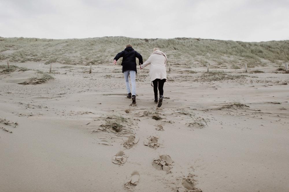 Couple running up dunes at beach