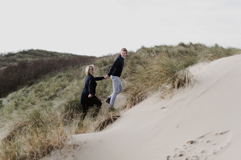 Couple running op dunes at the beach of Bloemendaal