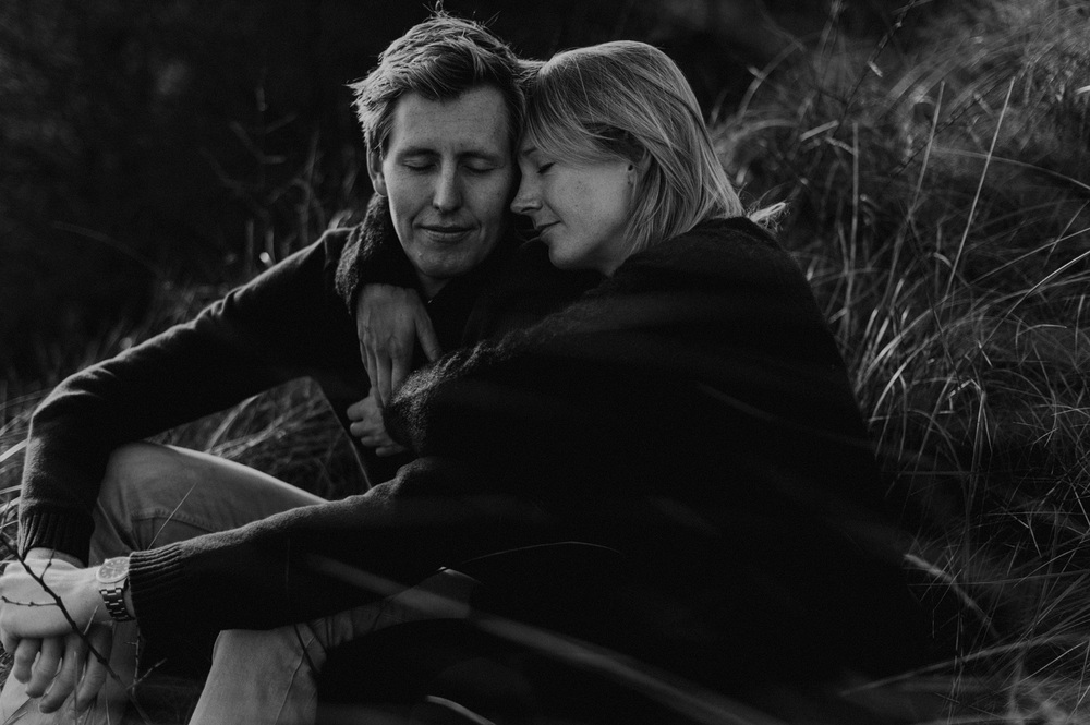 Couple sitting together in the dunes, close up black and white
