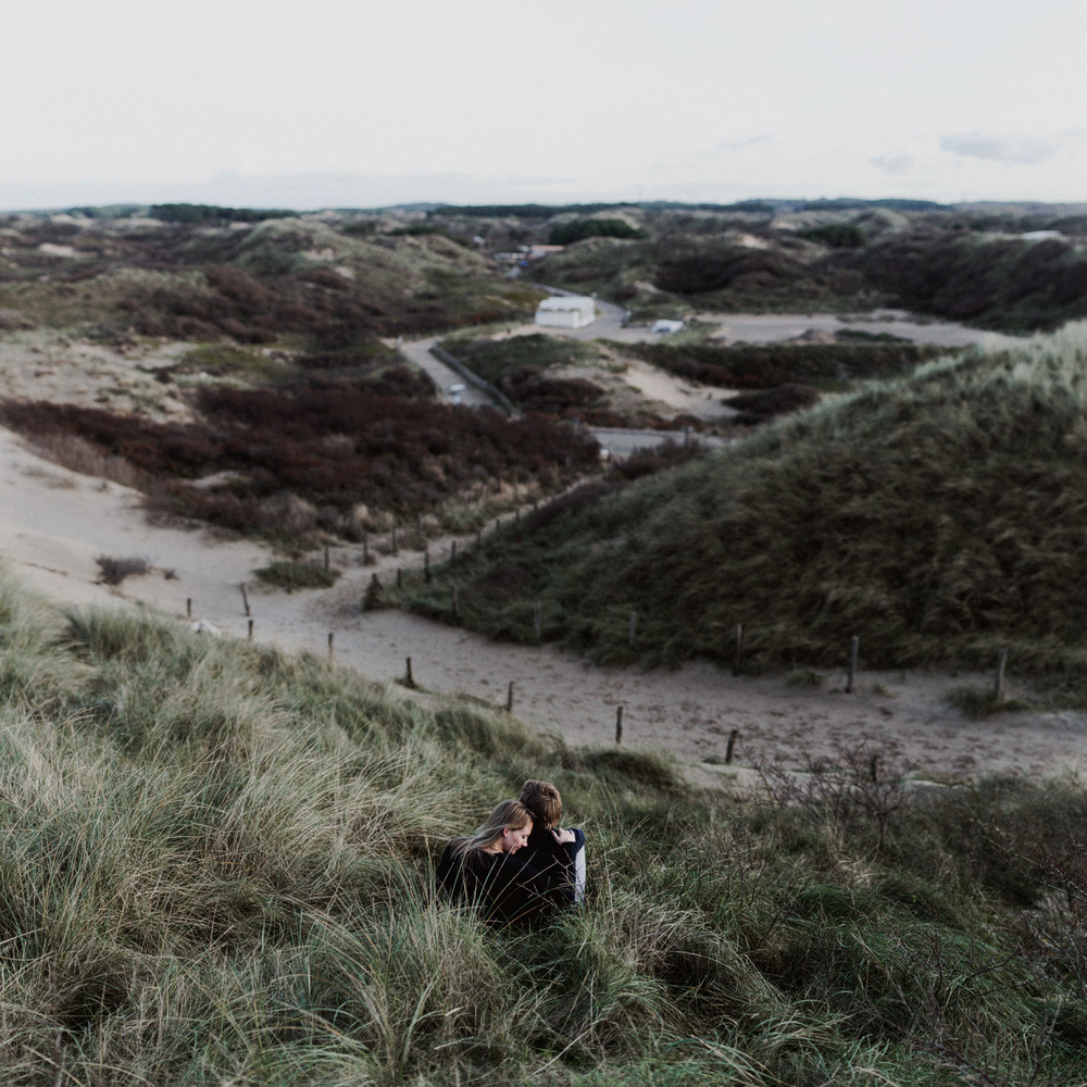 Couple sitting while facing view of dunes