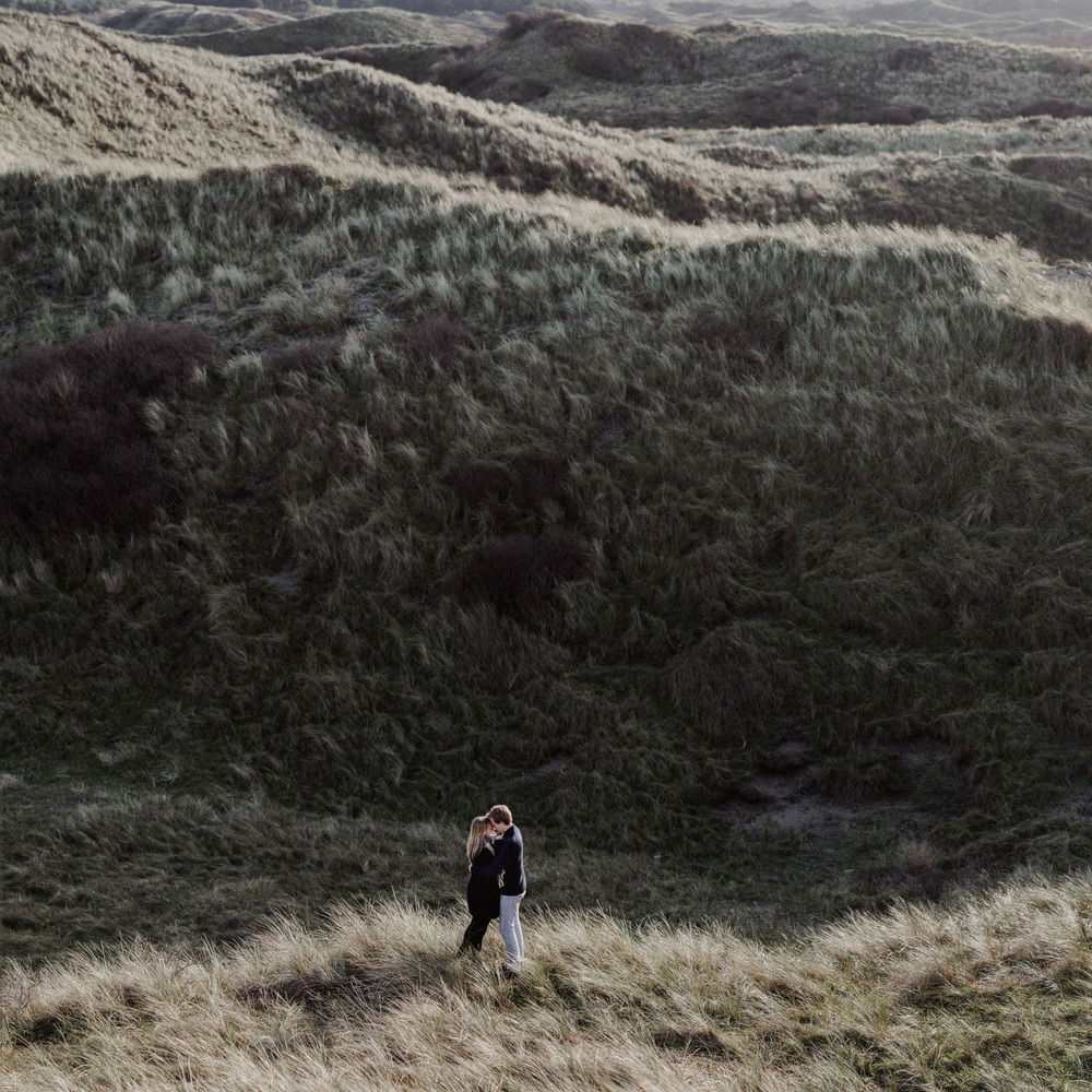 Couple far away facing each other in dunes