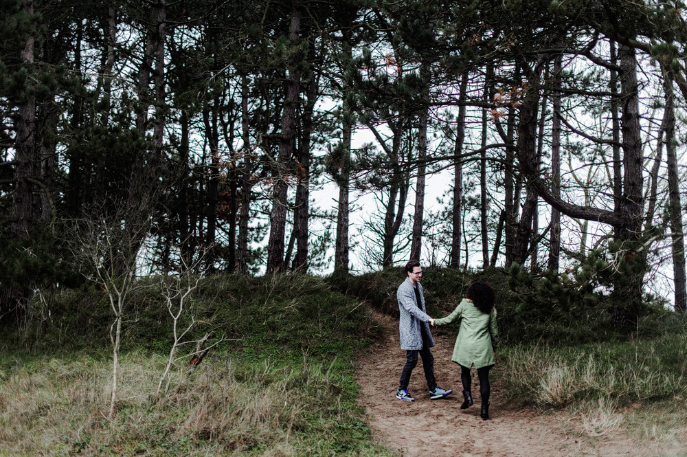 Couple holding hands and walking up dunes