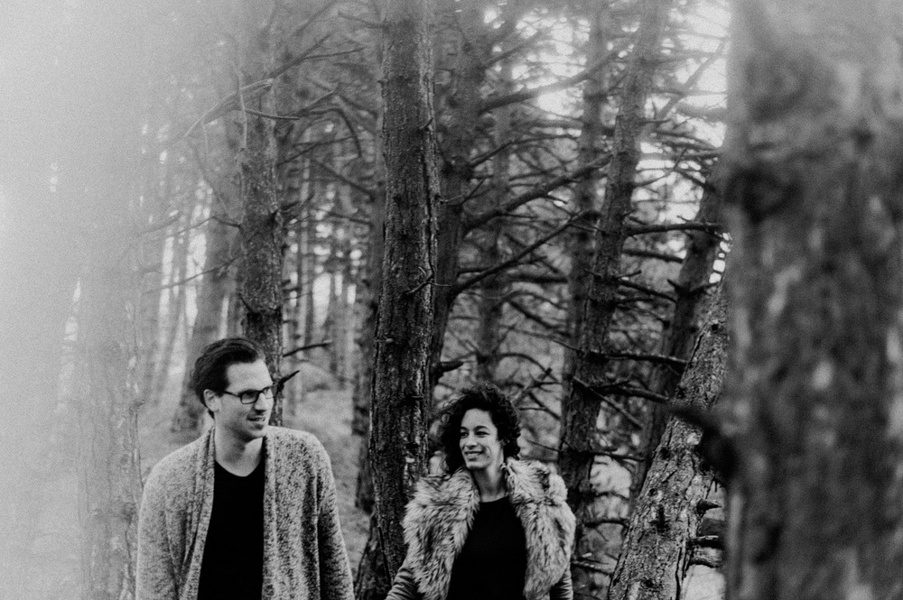 Couple walking in forrest smiling