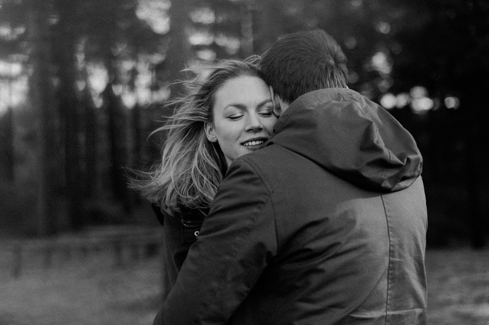 Girl smiling while hugging during couple session