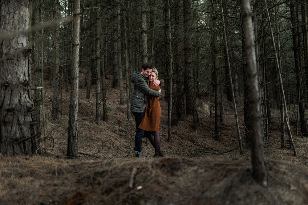 Couple hugging each other in the forrest