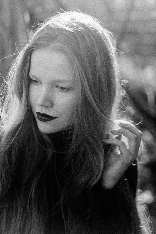 Fine art backlit portrait of girl touching her hair