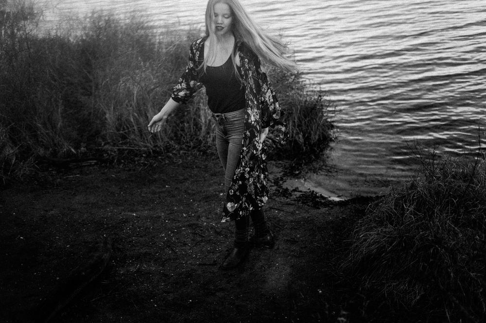 Fine art portrait of twirling girl near lake