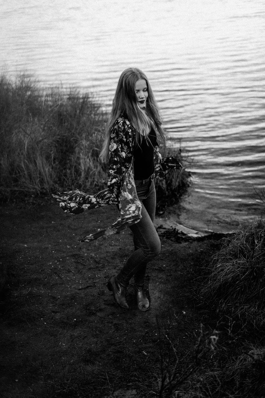Fine art portrait of dancing girl near lake