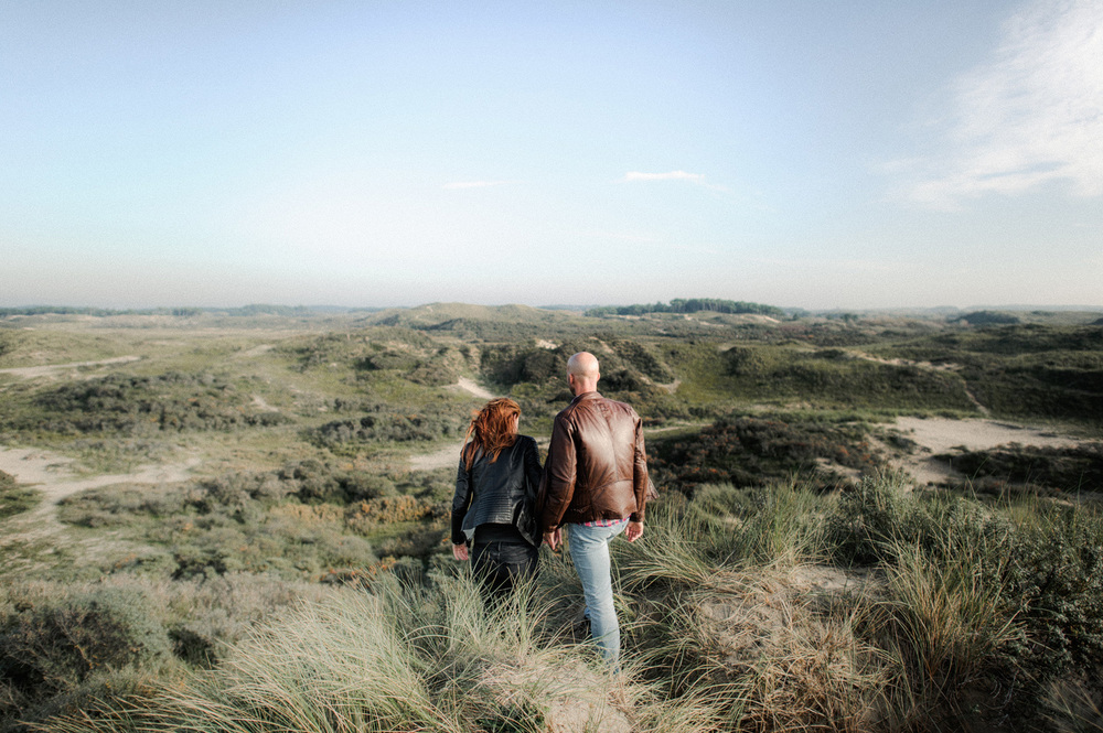 Couple walking away from camera into the dunes