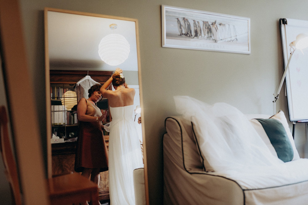 Bride putting on dress shot in mirror