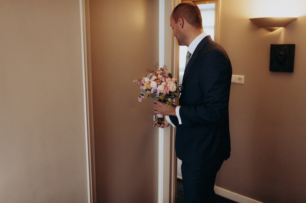 Groom with bouquet entering room with bride