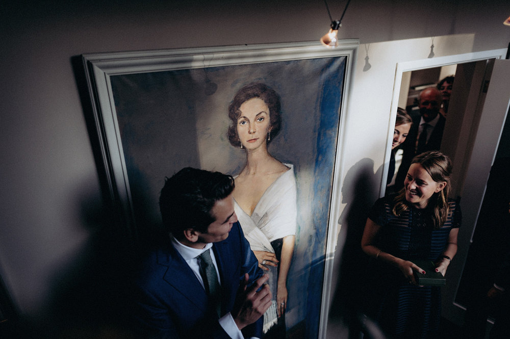 Wedding guests waiting in front of painting with woman