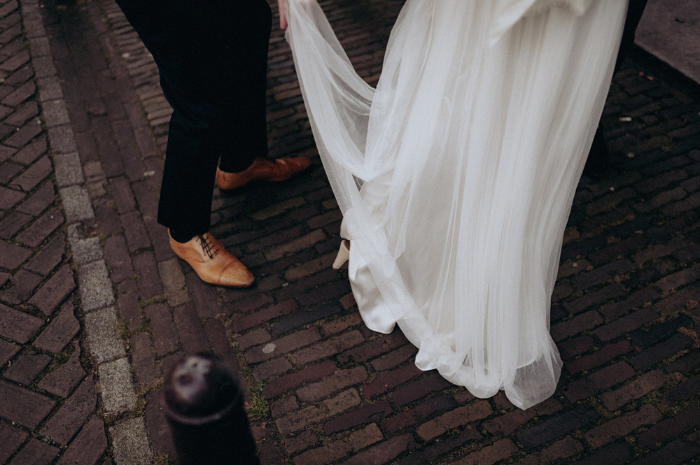 Groom holding wedding dress of bride on streets of Amsterdam