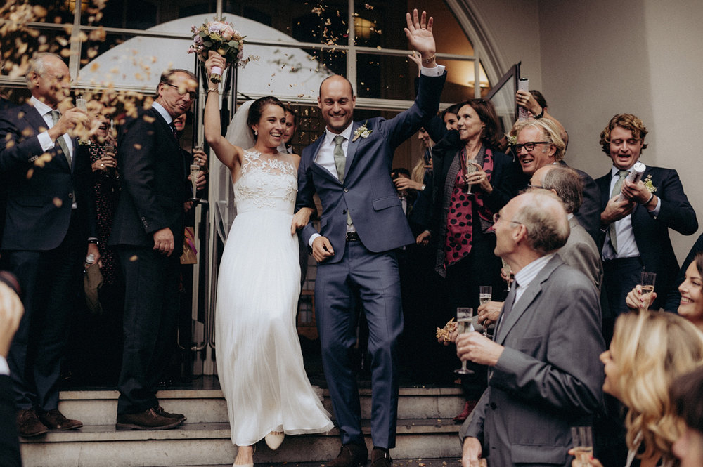 Bride and groom leaving Keizersgracht Kerk Amsterdam with happy faces