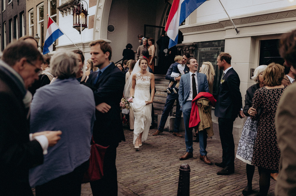 Wedding couple leaving Keizersgracht Kerk Amsterdam with dutch flags