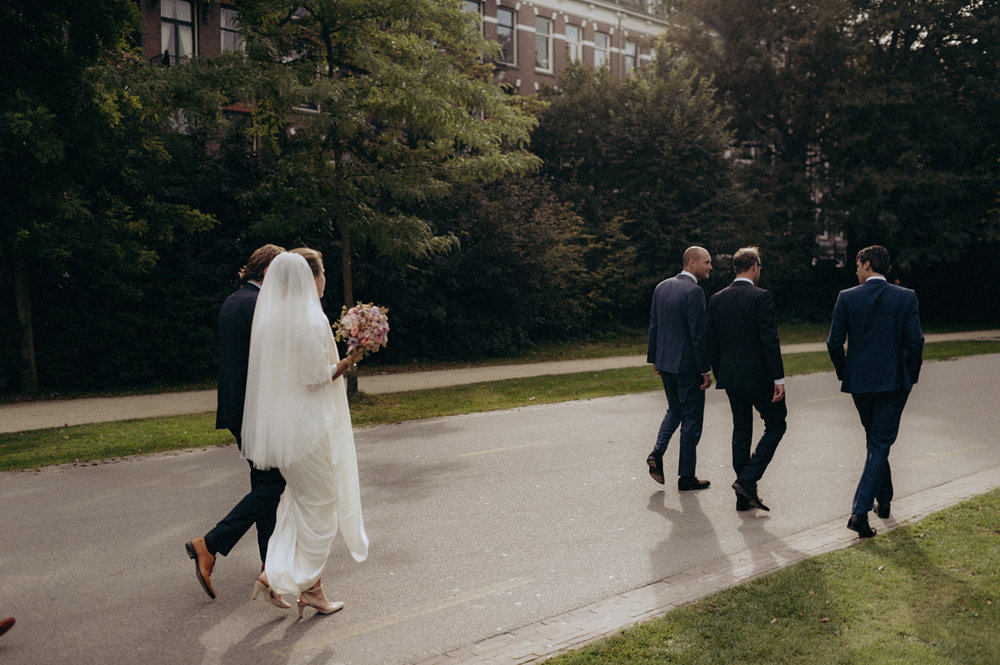 Wedding party with bride and groom walking in Vondelpark Amsterdam