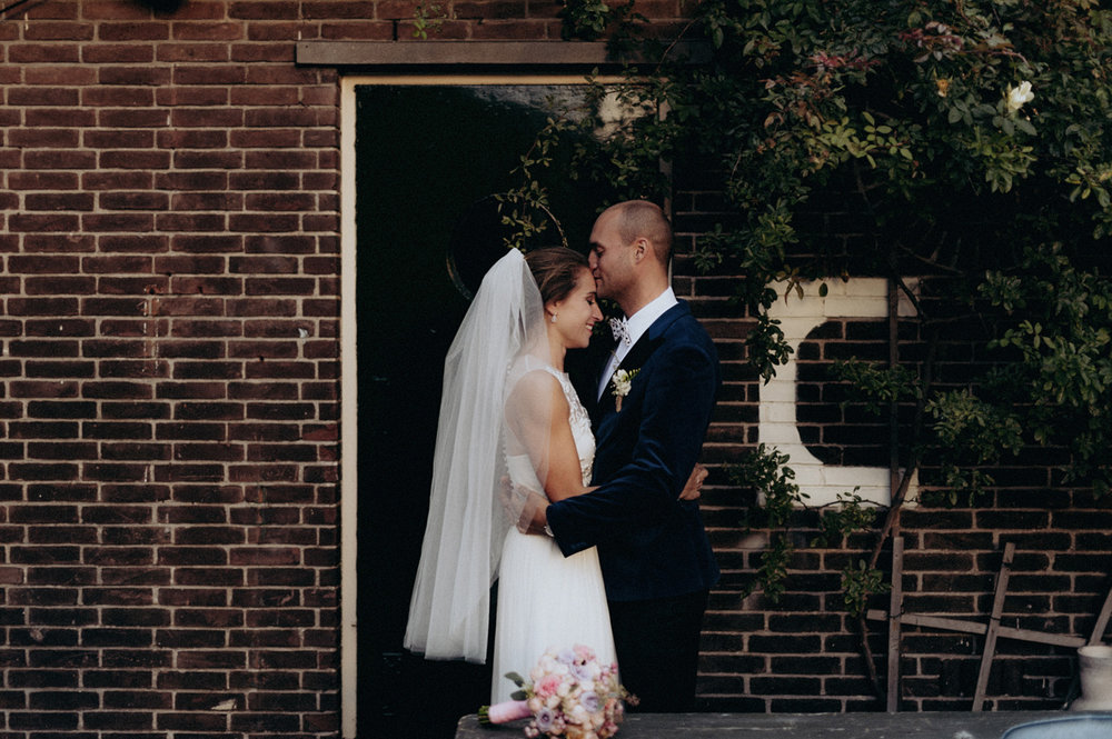 Groom kissing forehead of bride at Rijk van de Keizer