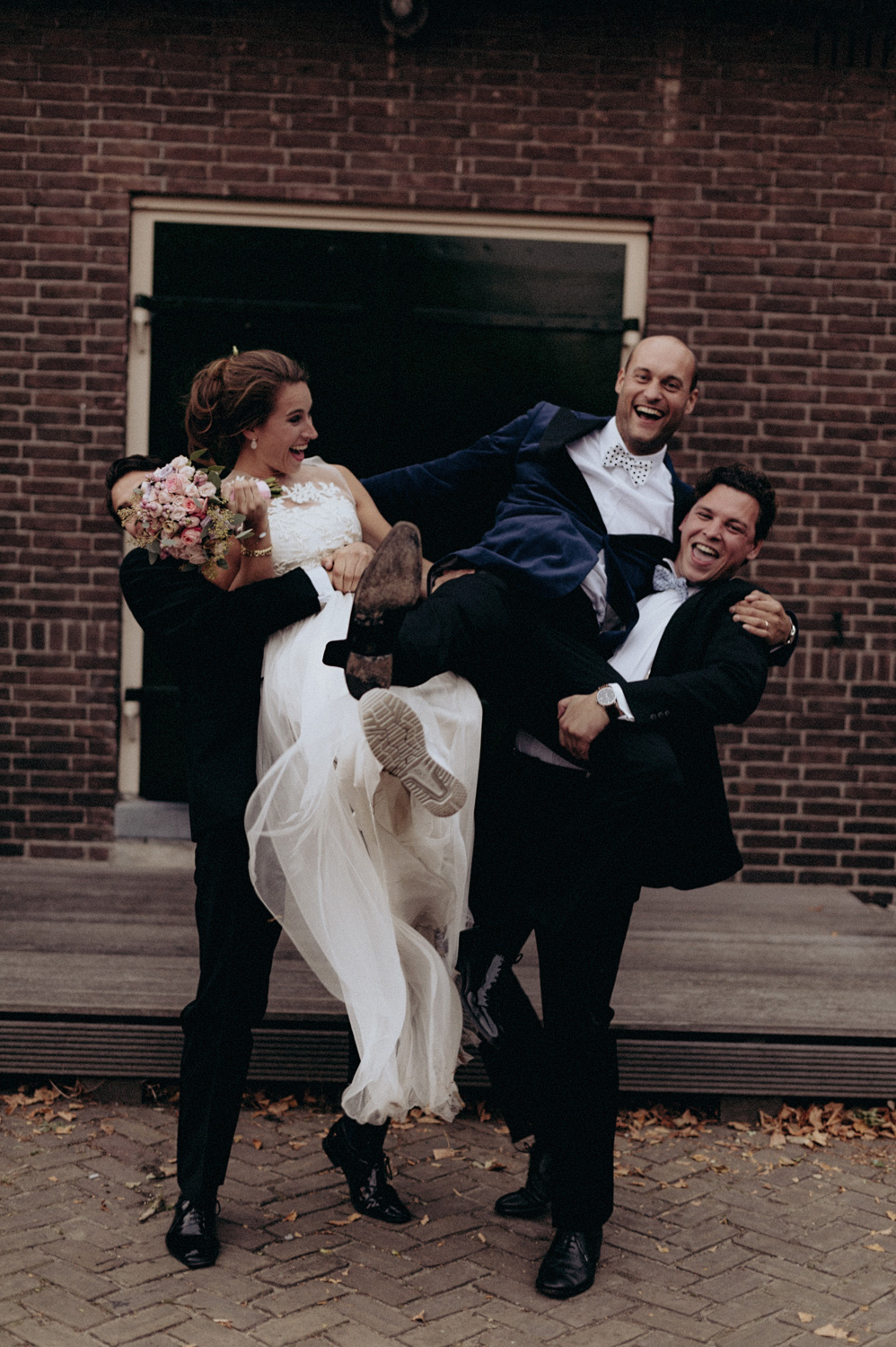 Bride and groom lifted in the air by wedding guests at Rijk van de Keizer
