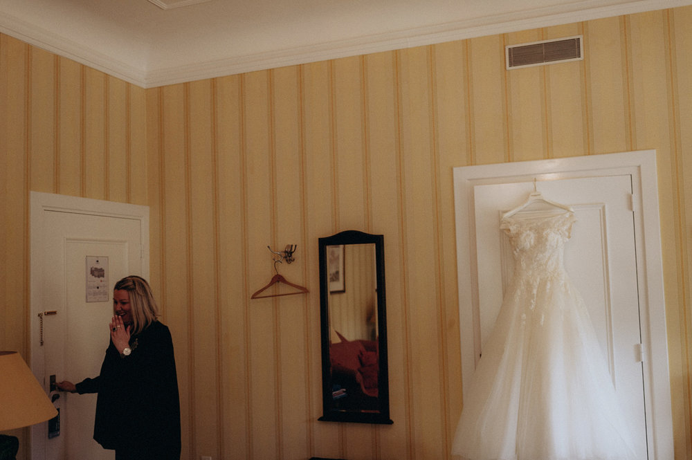 Dress of bride hanging on door
