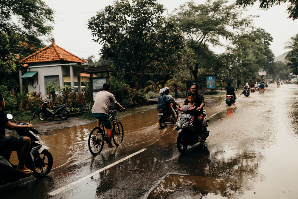 Scooters driving through rain in Bali, Indonesia