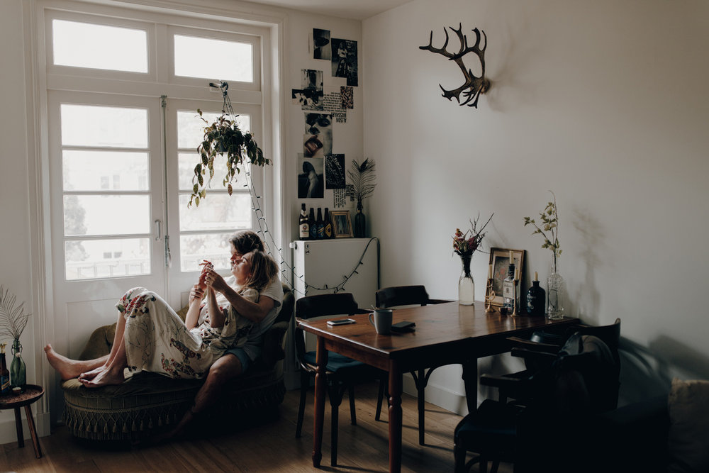 Couple lying on couch in front of window holding hands