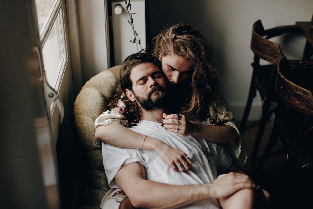 Guy with beard lying with his girlfriend on couch next to window