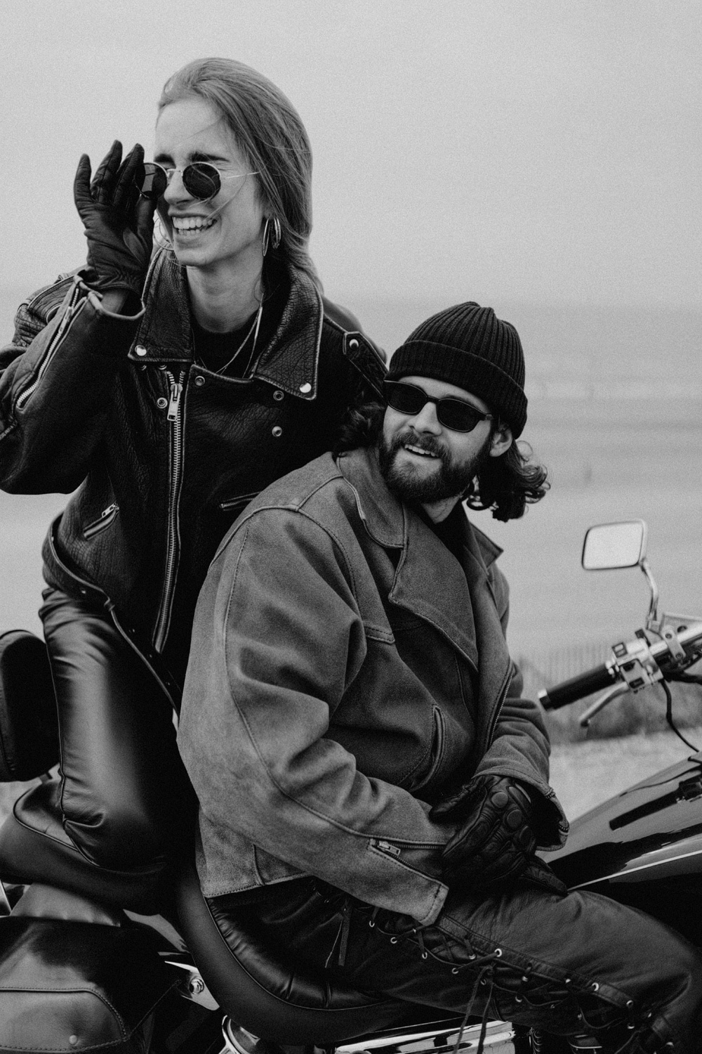 Biker couple sitting on motorbike smiling