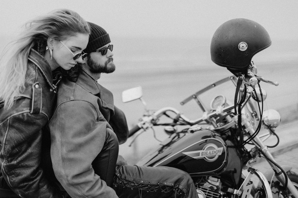 Girl sitting on the back of motorbike holding her boyfriend