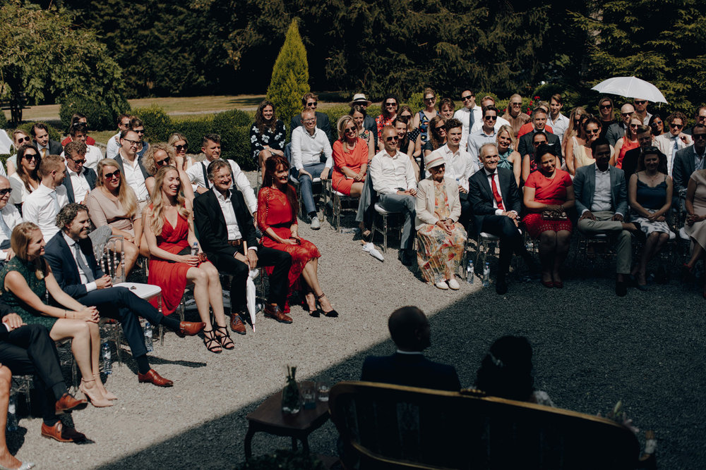 People in sun at wedding ceremony