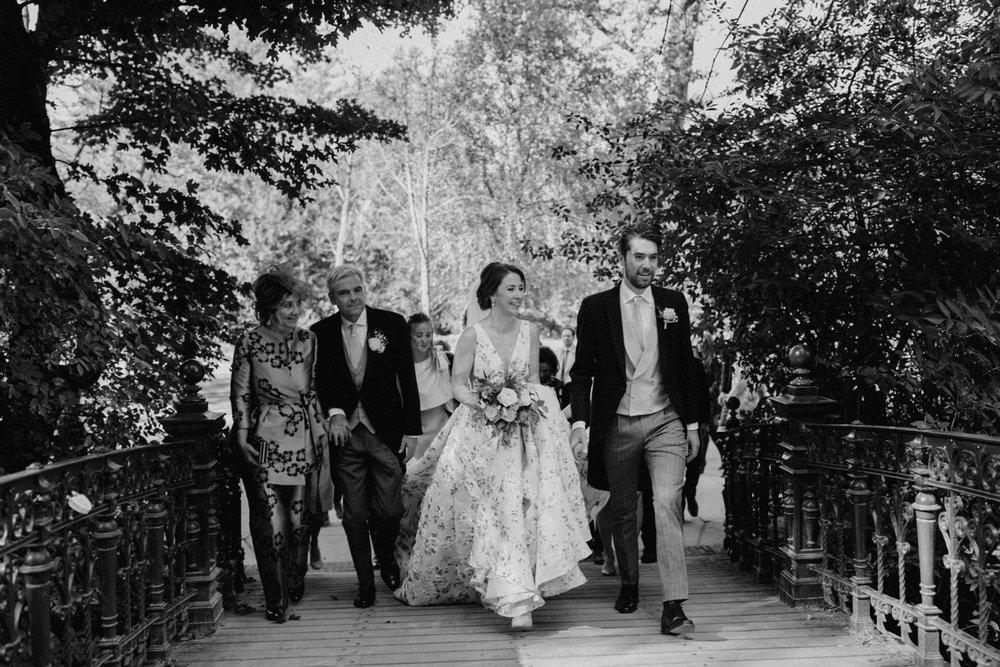 Bride and groom walking with wedding guests in Vondelpark Amsterdam