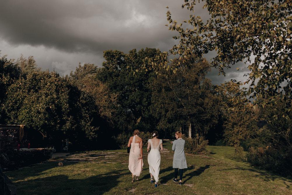 Bride walking in field with dark clouds