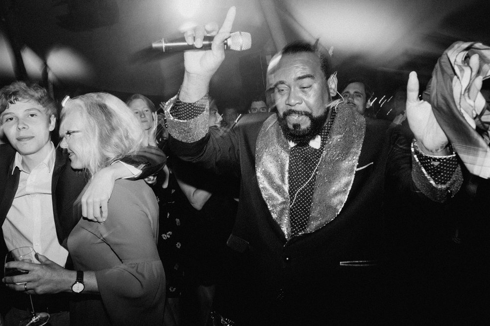 Barry White impersonator partying and hands in the air