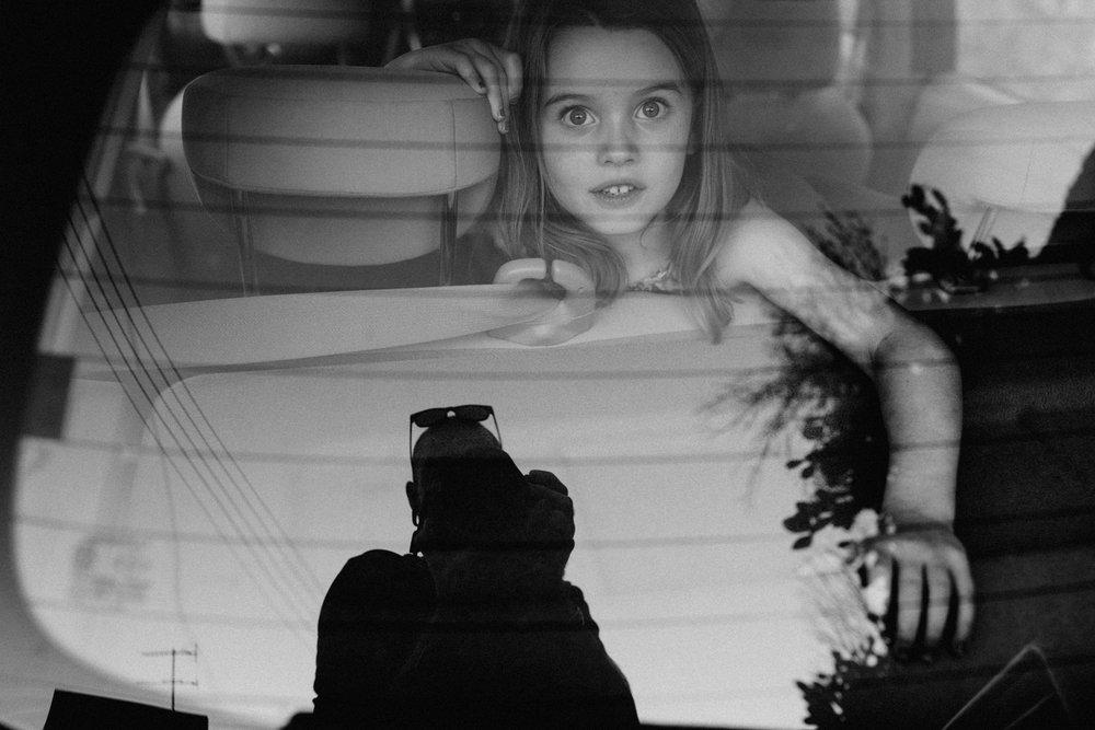 Little girl in car looking through backwindow