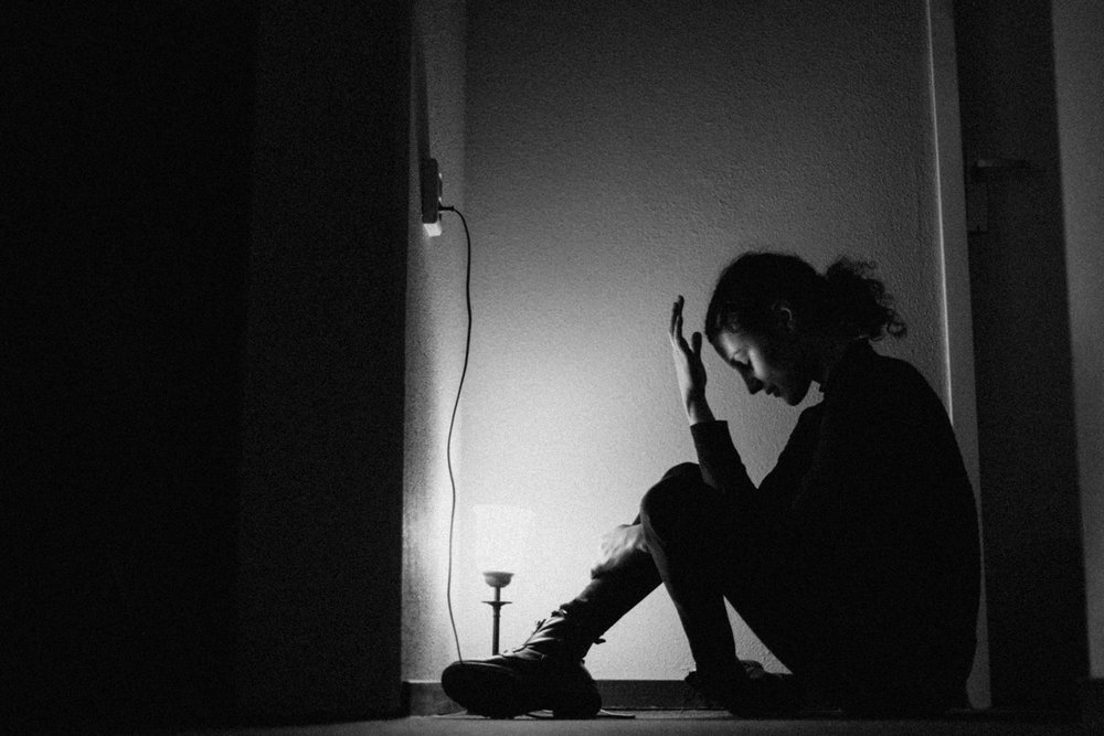 Girl sitting on floor with light and holding hand in front of her face