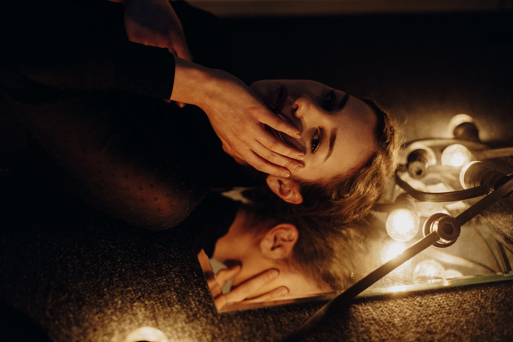 Girl lying on floor with face on mirror surrounded by string lights