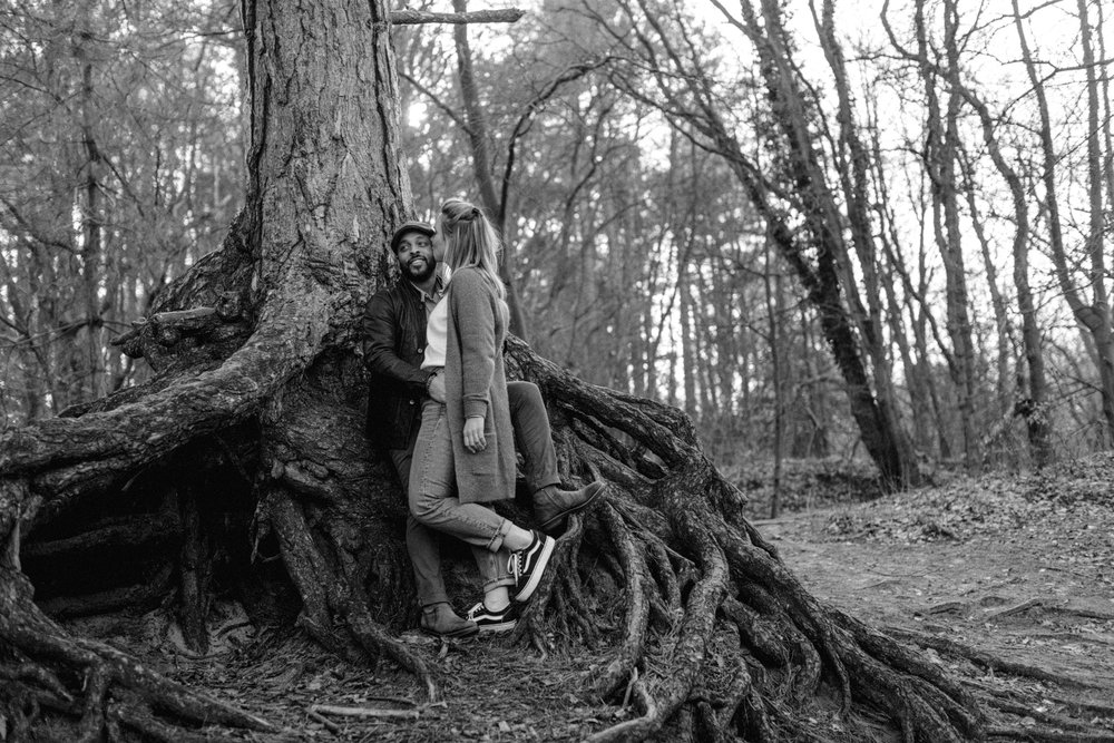 Guy and girl standing against tree with big roots