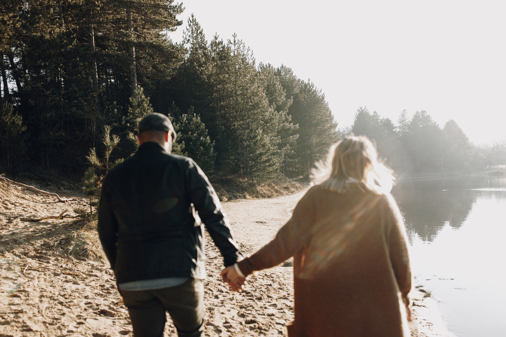 Couple walking holding hands at Oosterplas, Kennemerduinen