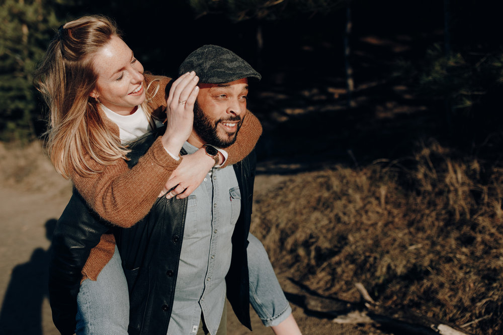 Girl jumping on the back of boyfriend while smiling