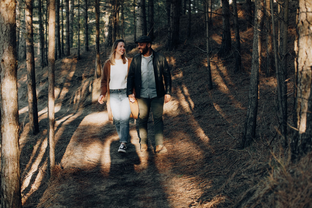 Couple facing the camera while walking in the forrest