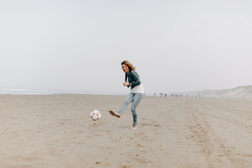 Pregnant woman playing soccer at the beach