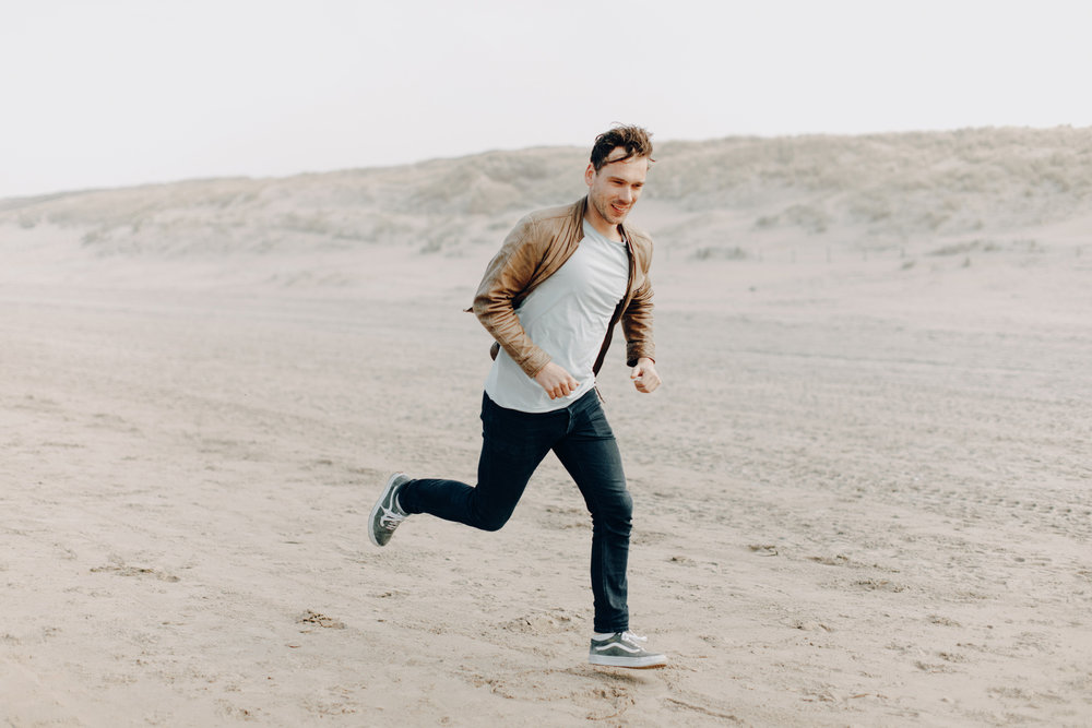 Guy running at the beach wearing leather jacket