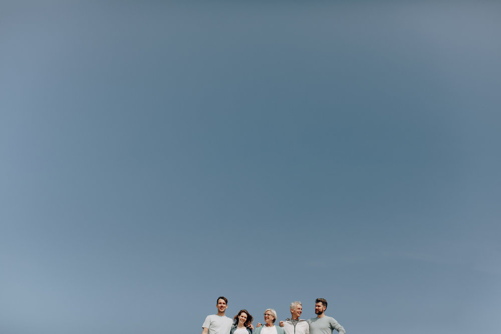 Blue sky with family posing for a picture