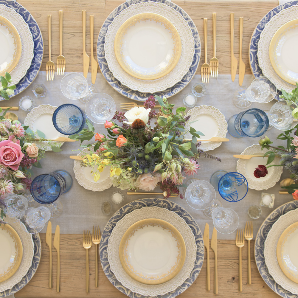 RENT: Blue Fleur de Lis Chargers + Lace Dinnerware in White + Versailles Glass Dinnerware in 24k Gold + Rondo Flatware in Brushed 24k Gold + Light Blue Vintage Goblets + Czech Crystal Stemware + Antique Crystal Salt Cellars  SHOP:Rondo Flatware in Brushed 24k Gold