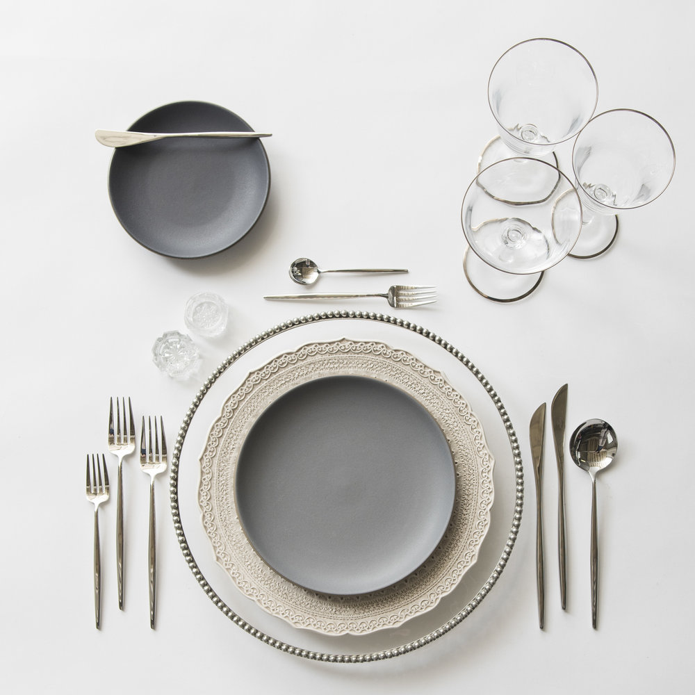 RENT: Pavé Glass Chargers in Pewter + Lace Dinnerware in White + Heath Ceramics in Indigo/Slate + Moon Flatware in Polished Steel + Chloe Platinum Rimmed Stemware + Antique Crystal Salt Cellars  SHOP: Moon Flatware in Polished Steel + Chloe Platinum Rimmed Stemware